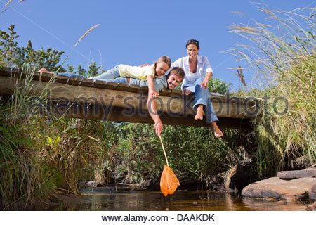 Smiling family with fishing net on footbridge over stream - Stock Photo