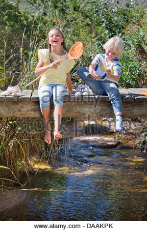 Happy boy and girl with fishing net removing shoes and socks on footbridge over stream - Stock Photo