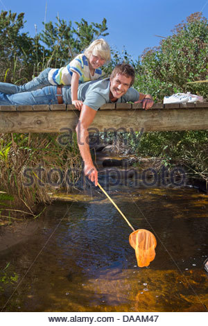 Portrait of smiling father and son laying on footbridge and dipping fishing net in stream - Stock Photo
