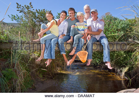 Portrait of smiling multi-generation family sitting barefoot on footbridge over stream - Stock Photo