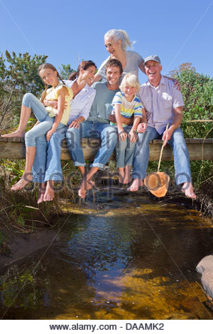 Portrait of smiling multi-generation family sitting barefoot on footbridge over stream - Stock Photo