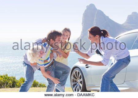 Mother photographing happy family playing outside car near ocean - Stock Photo