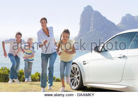 Happy family running outside car near ocean - Stock Photo