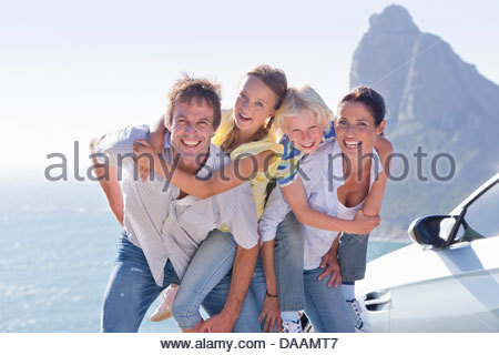 Portrait of enthusiastic family hugging outside car near ocean - Stock Photo
