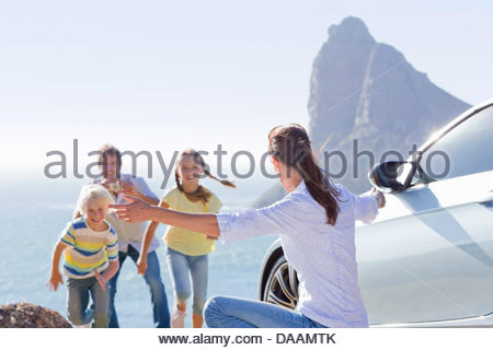 Family running toward woman with arms outstretched outside car near ocean - Stock Photo