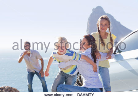 Playful family hugging outside car near ocean - Stock Photo