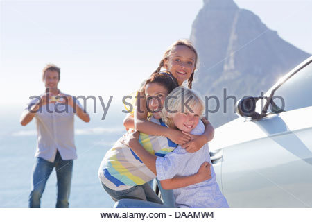 Portrait of happy family hugging outside car near ocean - Stock Photo