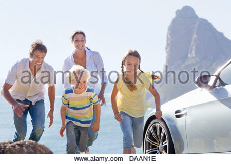Happy family running outside car near ocean - Stock Photo