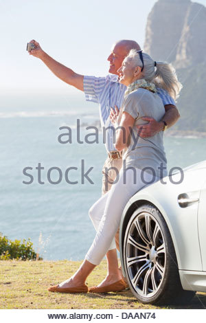 Couple leaning against car and taking self-portrait with camera near ocean - Stock Photo