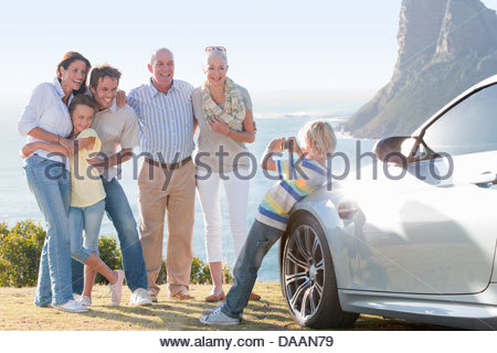 Boy photographing multi-generation family outside car near ocean - Stock Photo
