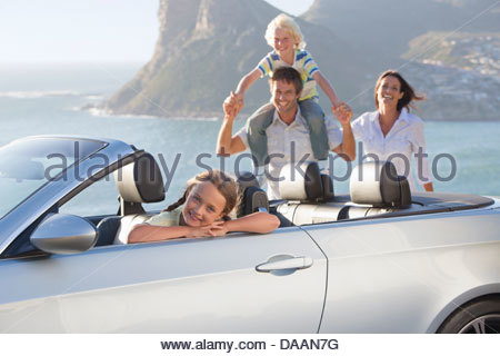 Portrait of happy family with convertible near ocean - Stock Photo