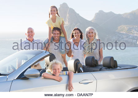 Portrait of happy multi-generation family with convertible near ocean - Stock Photo
