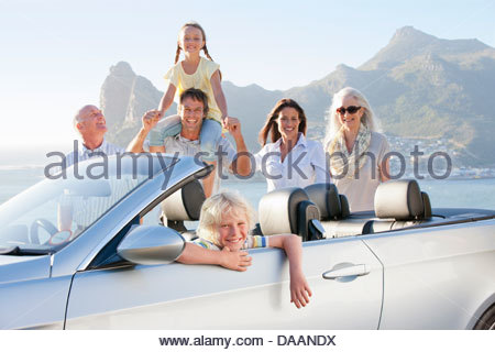 Portrait of smiling boy in convertible with multi-generation family and ocean in background - Stock Photo