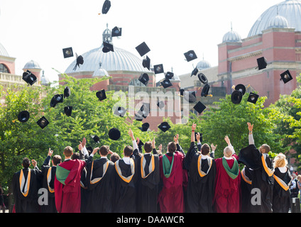 Graduates throw their caps in the air at Birmingham University, UK, after the graduation ceremony. - Stock Photo