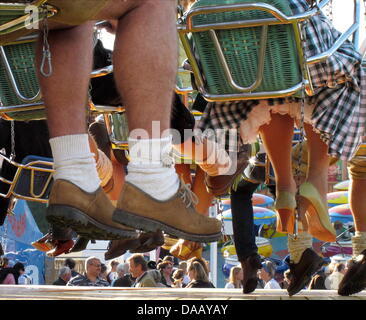 The legs of people wearing tradition costume on the flying chairs hang at the 178th Oktoberfest beer festival on - Stock Photo