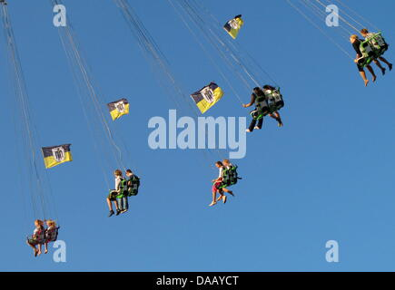 People swing through the aid in a blue sky on the flying chairs at the 178th Oktoberfest beer festival on the Theresienwiese - Stock Photo
