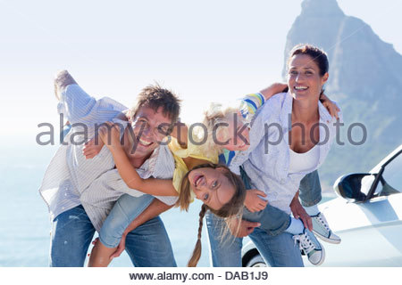 Portrait of happy family next to car with ocean in background - Stock Photo