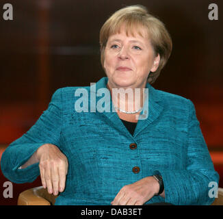 German Chancellor Angela Merkel sits in a chair prior to a talk show with German television presenter and broadcaster - Stock Photo