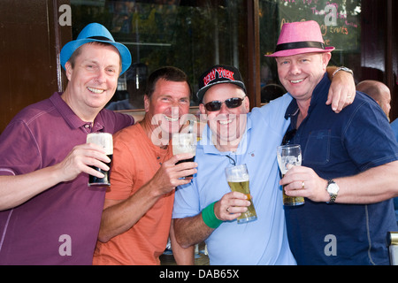 Friends in a stag party toasting and drinking pint / pints of beer on a Stag weekend in Dublin, Eire / Ireland. - Stock Photo
