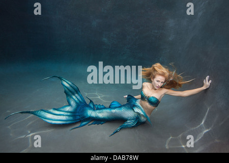 Young blond mermaid laying on the floor of a swimming pool in Virginia Beach, Virginia - Stock Photo
