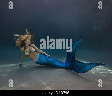 Young blond mermaid laying on the swimming pool floor in Virginia Beach, Virginia - Stock Photo
