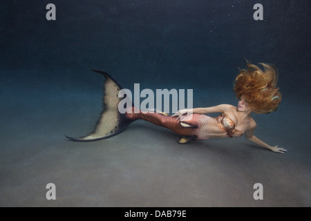 Young blond mermaid laying on the pool floor in a swimming pool Virginia Beach, Virginia - Stock Photo