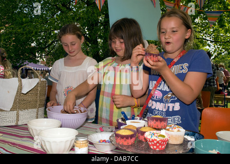 Youngsters at cake stall decorating/icing their own cake at a summer fete, East Meon, Hampshire, UK. - Stock Photo