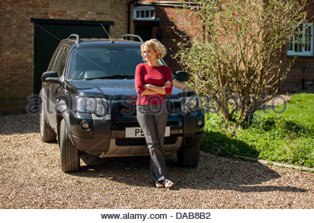 A mature woman standing in front of a car in the drive way of a house - Stock Photo
