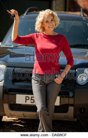 A mature woman holding the keys to her new car - Stock Photo