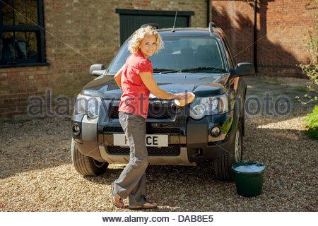 A mature woman washing a four wheel drive car - Stock Photo