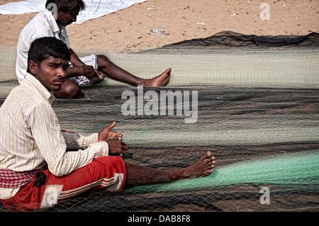 Fishermen fixing nets on the beach. Puri, Orissa, India - Stock Photo