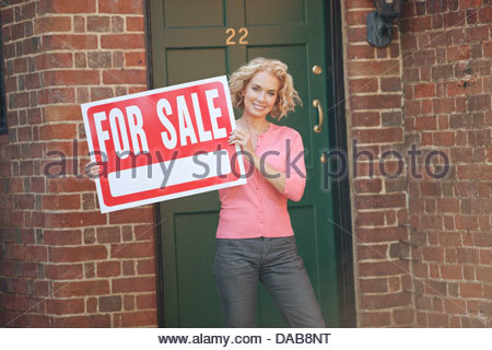 A mature woman holding a property for sale sign - Stock Photo