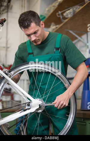 Mechanic or serviceman installing wheel on a bicycle in workshop - Stock Photo