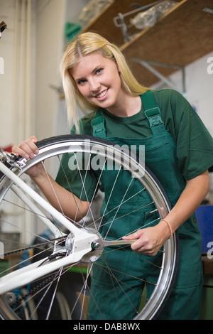 Female mechanic in workshop installing or repairing a bicycle wheel - Stock Photo