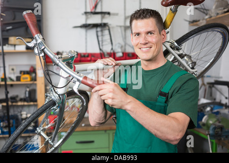 Bicycle mechanic carrying a bike in workshop smiling into the camera - Stock Photo