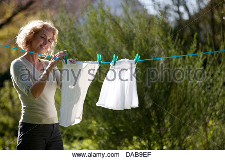 A mature woman pegging out washing on a washing line - Stock Photo