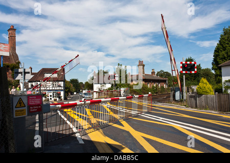 Barriers fall at an English level crossing as a train approaches in the New Forest,.Brockenhurst, Hampshire, England, - Stock Photo