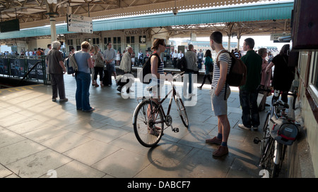 Passengers cyclists with bikes in summer awaiting train on Cardiff Central Railway Station platform in Wales UK - Stock Photo