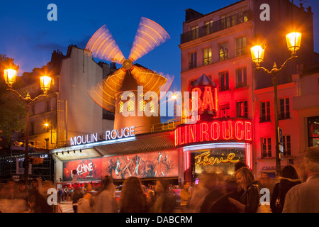 Tourists below the Moulin Rouge (1889), world famous Cabaret, Pigalle, Paris France - Stock Photo