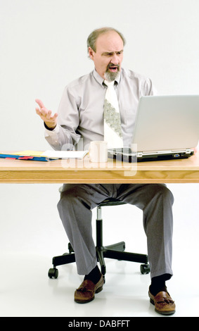 Businessman not liking the results he gets from computer calculations. - Stock Photo