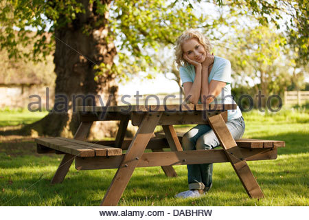 A mature woman sitting at a garden bench smiling - Stock Photo