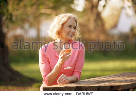 A mature woman sitting at a garden bench drinking a glass of wine - Stock Photo