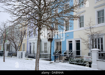 Pastel coloured houses on a snowy day in Elgin Crescent in the Notting Hill area of London, England, United Kingdom, - Stock Photo