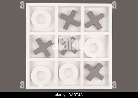 Wooden noughts and crosses game board in gray and white colors isolated in gray background - Stock Photo
