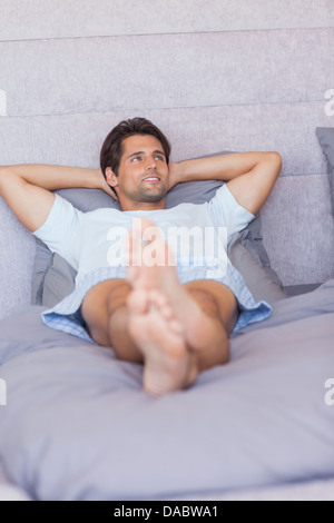 Man relaxing in his bed - Stock Photo