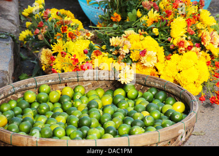 A basket full of fresh green asian limes and bouquets of mixed yellow field flowers in a market in Vietnam - Stock Photo