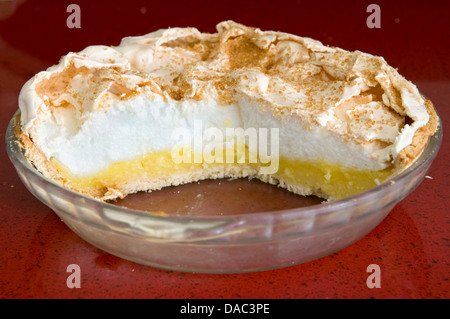 Home made lemon meringue pie in glass bowl on red worktop - Stock Photo
