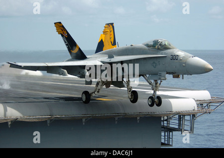 An F-A-18C Hornet launches from the flight deck of the conventionally powered aircraft carrier - Stock Photo