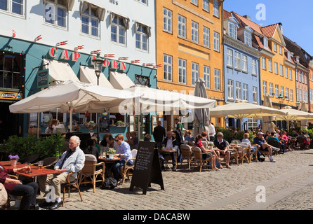 Outdoor cafés with people dining out enjoying sunshine on pedestrianised street in Nyhavn, Copenhagen, Zealand, - Stock Photo