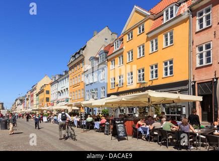 Pedestrianised waterfront street with outdoor cafes and colourful buildings in Nyhavn, Copenhagen, Zealand, Denmark, - Stock Photo